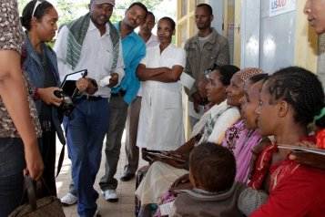 Me (sunglasses, iPad) in Ethiopia visiting health workers at a health post.