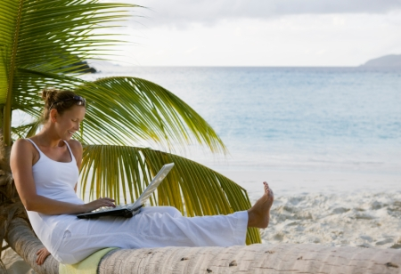 smiling woman using laptop on tropical beach