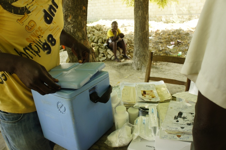 A Haitian mother waits her turn for her daughter be vaccinated.